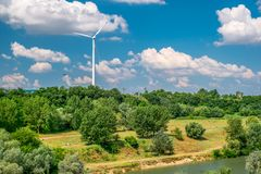 Wind turbine on the hill produces green clean energy. Panorama stock photos