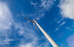 Wind turbine. A low angle view of a wind turbine under blue skies Royalty Free Stock Photos