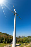 Wind turbine in Mountain with Sun Rays. Wind turbine with horizontal axis in mountain with green forest and a clear blue sky with sun rays. Verona Italy Royalty Free Stock Photos
