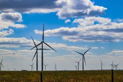 Wind turbine on Oklahoma prarie behind barbed wire fence - selective focus - under blue cloudy sky stock images
