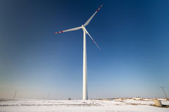 Wind turbine over blue sky. On winter field Stock Photography