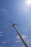 Wind turbine over blue sky. With sun in frame Royalty Free Stock Image