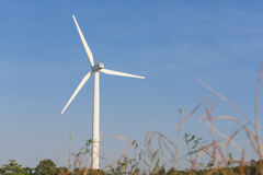 Wind turbine over blue sky background on a sunny day Stock Photography