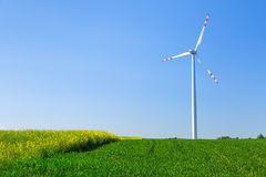 Wind turbine over blue sky. On the summer field Stock Photography