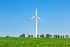 Wind turbine over blue sky. On the summer field Royalty Free Stock Photography