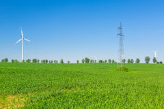Wind turbine over blue sky. On the summer field Royalty Free Stock Images