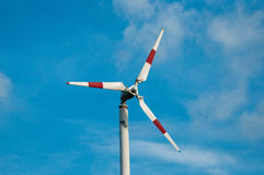 Wind turbine over the blue sky. White-red wind turbine over the blue sky Stock Photo