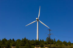 Wind turbine over the blue sky. Windmill on top of the mountain Stock Photo