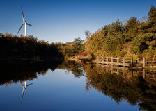 Wind turbine over lake royalty free stock photography