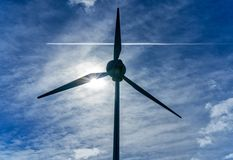 Wind turbine and passing aircraft, England royalty free stock image