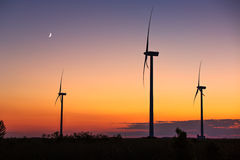 Wind turbine power generator silhouette at sunset Stock Images
