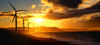 Wind turbine power generators silhouettes at ocean coastline. At sunset. Alternative renewable energy production in Philippines. Two images panorama, tilt shift Stock Photo