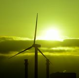 Wind turbine and power plant backlit at sunrise Stock Photos