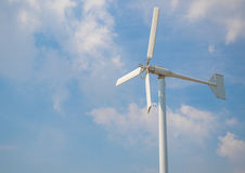 Wind turbine producing alternative energy on cloudy sky background Stock Images