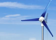 Wind turbine producing alternative energy renewable power on blue sky Royalty Free Stock Image