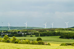 Wind turbine renewable energy source summer landscape with clear. Blue sky and a village or town in the foreground Royalty Free Stock Photos