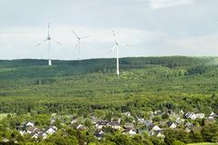 Wind turbine renewable energy source summer landscape with clear. Blue sky and a village or town in the foreground Stock Photos