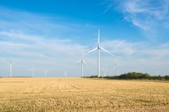 Wind turbine - renewable energy source. Wild mill in field with blue sky. Power and energy. Royalty Free Stock Photography