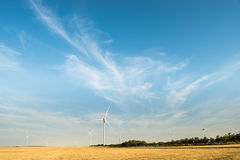 Wind turbine - renewable energy source. Wild mill in field with blue sky. Power and energy. Stock Images