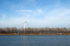 Wind-turbine on a riverbank Stock Image