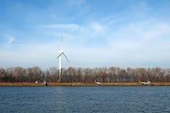Wind-turbine on a riverbank Stock Image