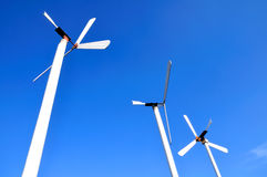 Wind turbine. Row of wind power generators on blue background Royalty Free Stock Photos