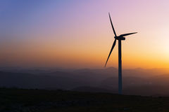 Wind turbine silhouette on mountain at sunset. Wind turbine silhouette on mountain at the sunset Stock Image
