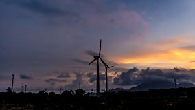 Wind Turbine silhouette on a sunset evening stock images