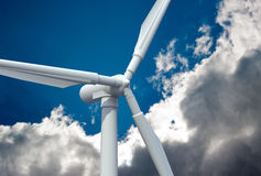 Wind turbine in the sky. Wind mill power generator against cloudy sky Royalty Free Stock Photography