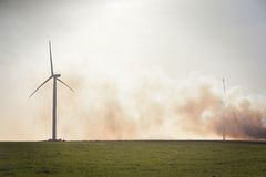 Wind Turbine. A small wind farm with smoke from a controlled fire concealing several turbines. One turbine remains clear as the wind blows the smoke further back Stock Image