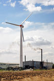 Wind turbine by smoking pipe. Wind turbine by the smoking pipe of the factory Royalty Free Stock Photo