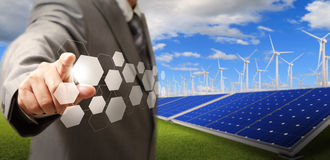 Wind turbine and solar farm. Business man hand point virtual buttons and wind turbine and solar farm as concept Royalty Free Stock Photo