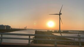 Wind turbine and solar panel farm in green energy and renewable energy farm. Shot during sunset.
