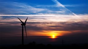 Wind turbine by sundown stock video footage