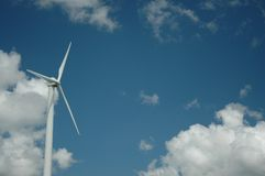 Wind turbine in sunny day, alternative energy. Wind turbine against blue and cloudy sky Stock Photography
