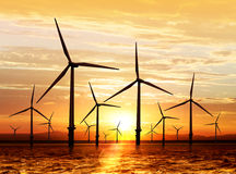 Wind turbine on sunset. Silhouette of wind turbine generating electricity on sunset Stock Photos