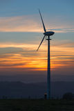 Wind turbine at sunset. A wind turbine in area of natural beauty at sunset royalty free stock image