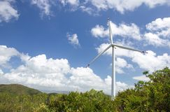 Wind turbine system to produce green electricity for renewable energy at power station. Lamma island, Hong Kong with mountain and blue sky background and copy royalty free stock image
