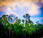 Wind turbine in trees. Metal wind turbine on rusty pole in green trees with blue skies Stock Photography