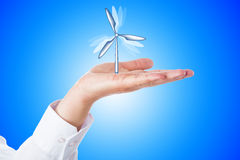 Wind Turbine Turning In A Palm On Blue Background Royalty Free Stock Photography