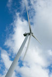 Wind turbine under cloudy sky. Royalty Free Stock Image