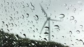 Wind turbine viewed through a glass in rainy weather stock video