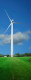 Wind turbine w/ path. Vertical view of a wind turbine on a green field. Cloudy sky background. (includes turbine path Stock Photos