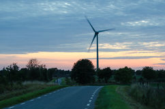 Wind turbine by a winding road at late evening Royalty Free Stock Photo