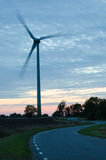 Wind turbine at winding road in a rural landscape Stock Image