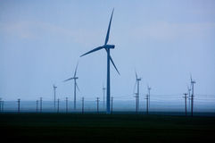 Wind Turbines. Group of wind turbines and power lines on a rainy day Stock Images