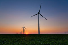 Wind Turbines. In a field at sunset Royalty Free Stock Photo