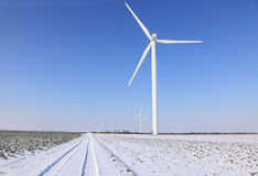Wind turbines. Image of a small road between  wind turbines in a plain covered by snow in winter Royalty Free Stock Photography