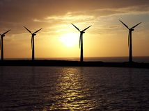 Wind Turbines. Illustrated wind turbines over a photo of sky and sea Stock Images