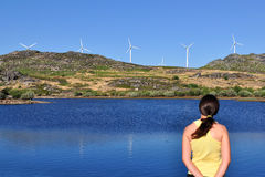 Wind Turbines. Woman looking at a wind mill across a lake. Focus is on the wind turbines and the woman is slightly out of focus Royalty Free Stock Photography